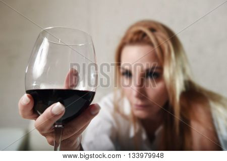 blond sad and wasted alcoholic woman sitting at home sofa couch drinking red wine holding glass completely drunk looking depressed lonely and suffering hangover in alcoholism and alcohol abuse