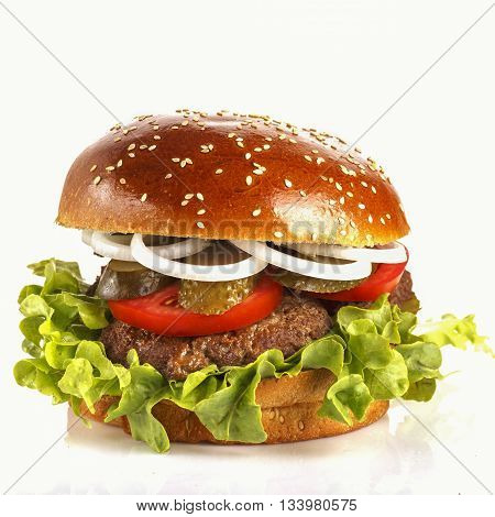 Juicy appetizing burger with pickled cucumber tomato and onion.