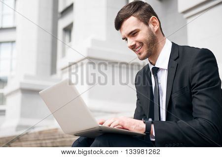 Like my work. Cheerful delighted smiling man sitting on the footsteps and expressing gladness while using laptop