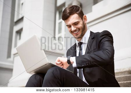 What time is it. Pleasant cheerful smiling businessman sitting on the footsteps and using his smartwatch while working on the laptop
