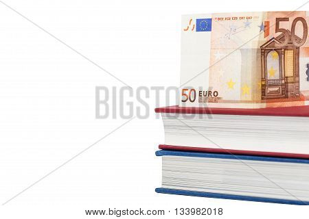 Euro money banknotes on books over white background. Isolated with clipping paths. Focus on left part of the books and banknote