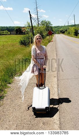 A beautiful young blond woman walking along a street with her suitcase in the country side on a bright summer day.