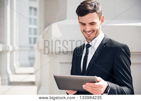 Modern way of life. Cheerful content smiling man using tablet and expressing gladness while leaning on the wall