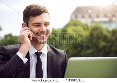 Pleasant interlocutor. Cheerful delighted smiling man using laptop and talking on cell phone while resting outdoor