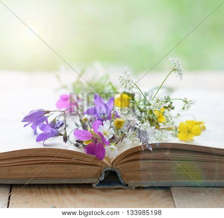 Vintage book with bouquet of wild flowers nostalgic vintage background