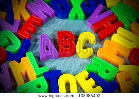Close up of a colorful magnetic letters on a wooden desk. Illuminated ABC text