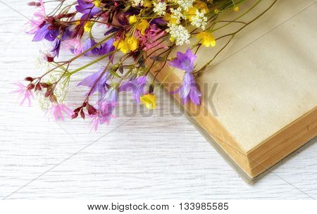 Vintage opened book with bouquet of wild flowers, nostalgic vintage background