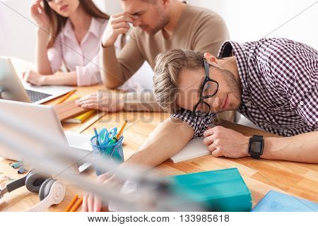 Exam time has gotten to him. Top view of young student sleeping on his desk after tiring study session with friends in background