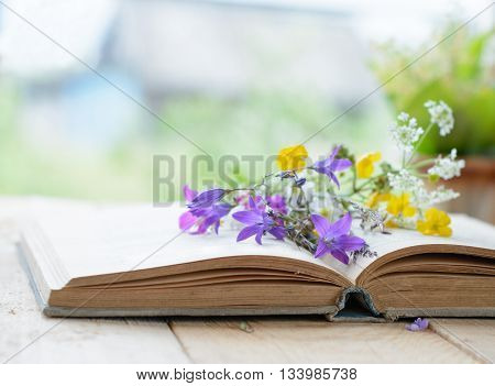 Vintage book with bouquet of wild flowers, nostalgic vintage background