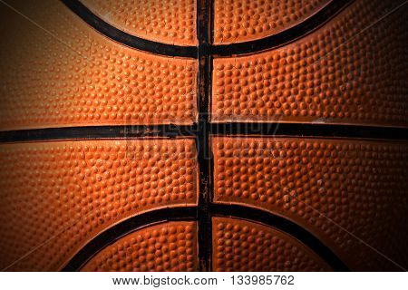 Macro photo of an old black and orange basketball with shadows
