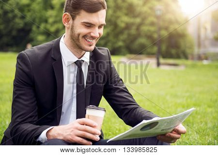 In the whirlwind of information. Cheerful handsome content man reading newspaper and drinking coffee while resting on the grass