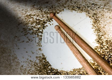 Macro photo of an old and worn snare drum with wooden drumsticks with wooden tip