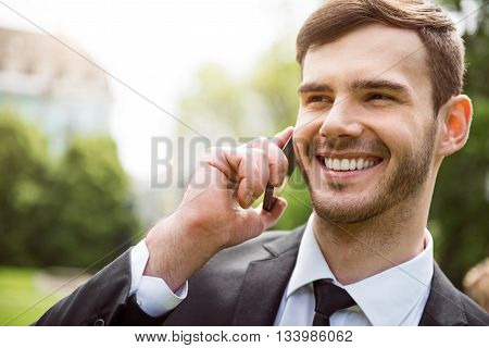 Pleasant call. Portrait of pleasant delighted handsome man holding cell phone and talking on it while expressing gladness