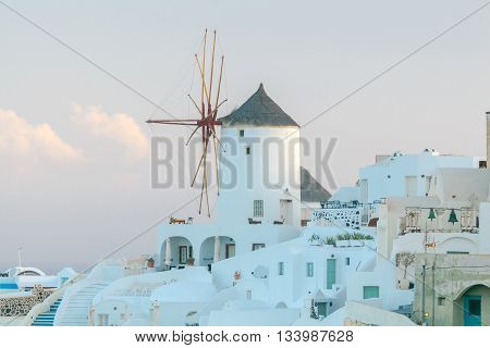 White windmills at sunset in the village Oia. Santorini. Greece.