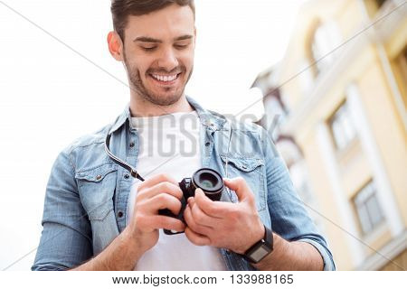 Ready to make shots. Positive smiling man holding photo camera and going to take photos while expressing gladness