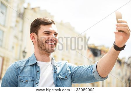 Say cheese. Positive handsome smiling man holding cellphone and making selfie while expressing gladness