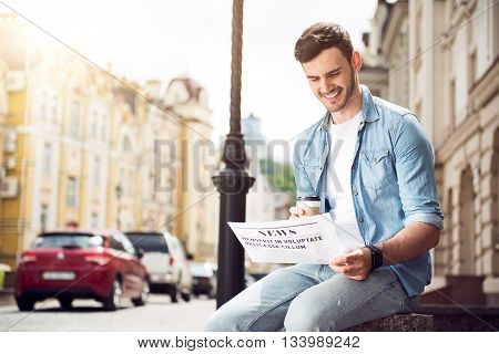 Daily press. Pleasant handsome delighted man sitting in the street and reading newspaper while drinking coffee