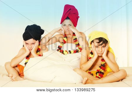 mother and two sons sitting in bed with german colors and looking disappointed