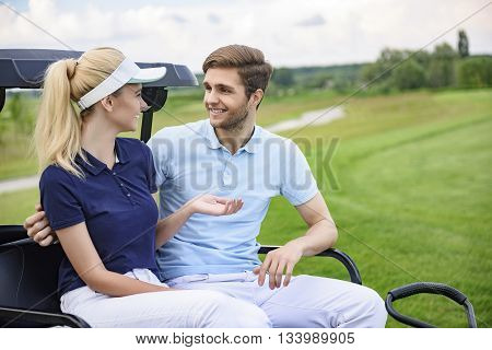 Couple ready to play golf. Attractive golfing couple smiling and looking at each other, discussing game