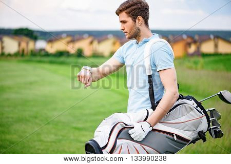 Checking time. Young guy looking at his smartwatch, standing on golf course and holding golf bag
