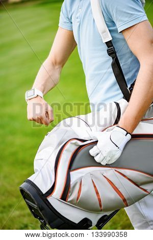 Exactly on time. Close up of young golfer checking time on beautiful golf course, holding his bag while walking to next hole