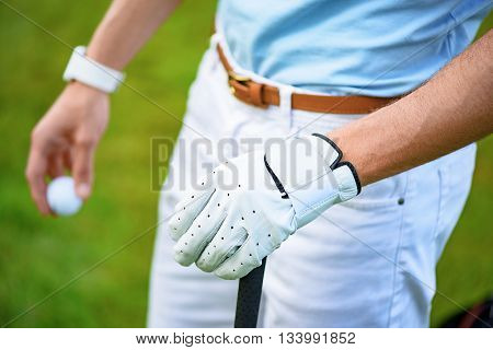 Let go golfing. Close up of hands of male golfer, holding golf ball in one and golf club in another