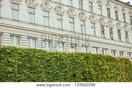 beautiful white building in Ljubljana over green natural fence