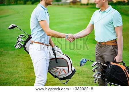 Congratulations on your game. Close up of golfing partners shaking hands after game of golf, standing on golf course, holding golf backs