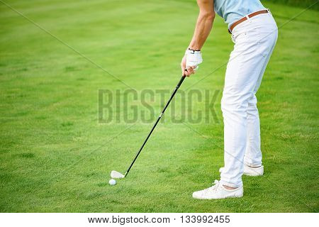 Ready to play. Close up of golfer playing golf on course, holding his club, ready making impact