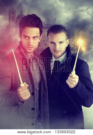 two young wizards holding a magic wand