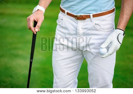 Ready for game. Close up of golf player standing on golf course and holdinf driver, white golf ball
