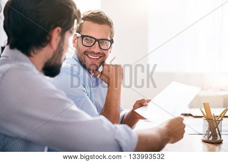 Here you are. Positive delighted smiling colleagues sitting at the table and holding papers while being involved in work