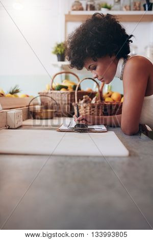 Female Juice Bar Owner Calculating Expenses