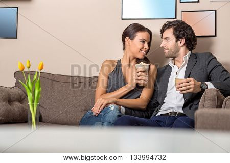 A beautiful young couple siting on the sofa in a coffee shop and enjoying there coffee.