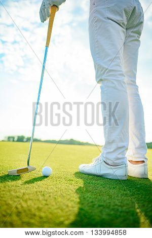 It will be long day on course. Close up of golfer standing on course and holding driver during sunny day