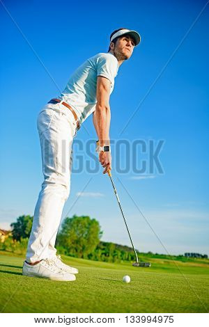 One shot to success. Young golfer playing golf while standing on green and looking into distance, holding driver