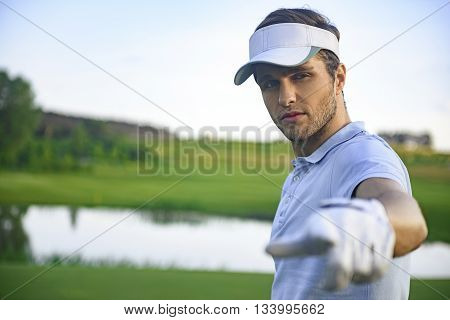 I inviting you to my team. Young golf player pointing finger at camera, standing on green course