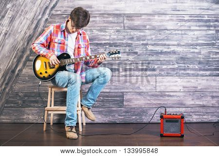 Casual young man sitting on chair in studio with wooden floor and wall playing electric sunburst guitar connected to amplifier