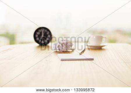Front view of blurry office desktop with coffee cup crumpled paper ball clock and pen on light background