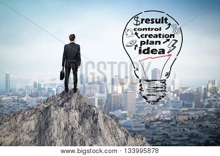 Business idea concept with abstract lightbulb sketch and thoughtful businessman on mountain top looking at city
