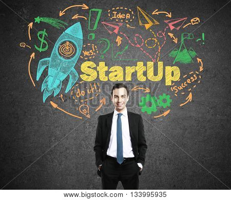 Startup concept with confident young businessman and colorful rocket ship sketch on concrete background