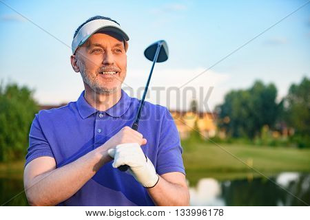 Considering his next shot. Mature male golfer thinking about his next play, holding his golf club over his shoulders