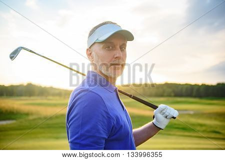 Confidence with club. Mature golfer with his club resting on his shoulders considering his next shot