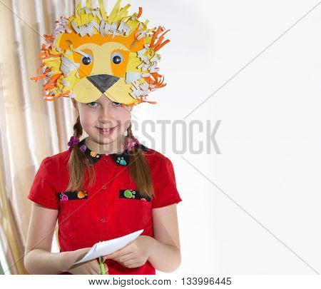 Little girl demonstrating her art craft works, Paper masher fairy castle and Lion mask she made. Educational and creative concept.