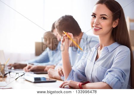 Positive thinking. Positive delighted beautiful smiling woman sitting at the table and expressing gladness while her colleagues working in the background