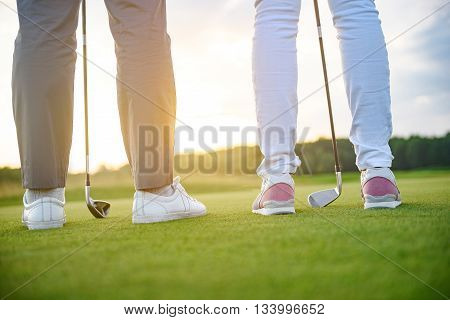 Ready to play golf. Close up of two golfers ready to tee off on golf field, holding drivers