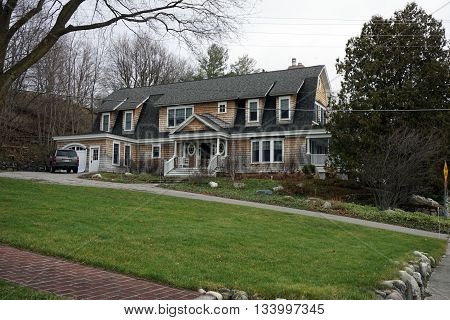HARBOR SPRINGS, MICHIGAN / UNITED STATES - DECEMBER 24, 2015: A large home under the bluff on Fourth Street in Harbor Springs, Michigan, during December.