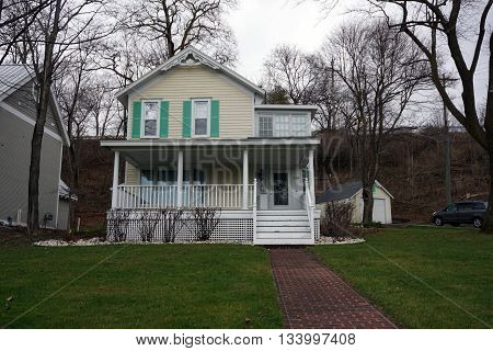 HARBOR SPRINGS, MICHIGAN / UNITED STATES - DECEMBER 24, 2015: A yellow Victorian home under the bluff on Fourth Street in Harbor Springs.