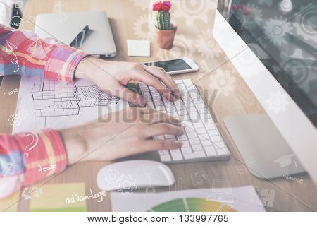 Side view of male hands using computer keyboard on wooden office desktop with construction sketch and other items with abstract cogwheels layer