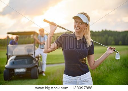 She enjoying golfing as hobby. Smiling young girl holding her golf club while on course with boyfriend and golf cart in background